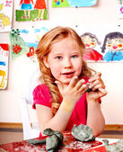 Child girl with clay in play room. — Stock Photo