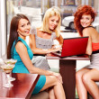 Women at laptop drinking cocktail in a cafe. — Stock Photo
