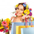 Woman with shopping bag holding flower. — Stock Photo