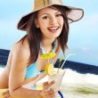 Girl in bikini drink juice on beach. - Stock Photo