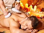 Man getting herbal ball massage treatments . — Stockfoto