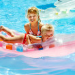 Children swimming on inflatable beach mattress. - Stock Photo
