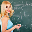 Schoolchild writing on blackboard. — Stock Photo
