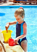 Child with bucket in swimming pool. — Stock Photo
