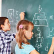 School child writting on blackboard. - Stock Photo