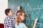 School child writting on blackboard. — Stock Photo