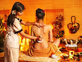 Woman getting thai herbal massage ball. — Stockfoto