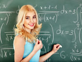 Schoolchild writing on blackboard. — Stock Photo