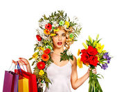 Kvinna med shopping väska håller blomma. — Stockfoto