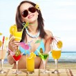 Girl in bikini on beach drinking cocktail. - Foto de Stock