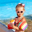 Child drinking  near swimming pool. - Foto Stock