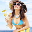 Girl in bikini drinking alcohol coctail through a straw. - Foto Stock