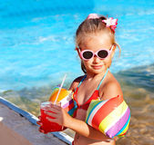 Child drinking near swimming pool. — Stock Photo