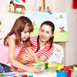 Child with teacher draw paints in play room. — Stock Photo #25256965
