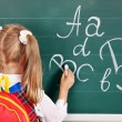 图库照片: Schoolchild writting on blackboard