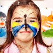 Stock Photo: Child with face painting in play room.