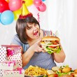 Woman eating hamburger at birthday. — Stock Photo #25257127