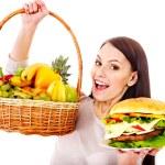 女性フルーツとハンバーガー間の選択 — ストック写真