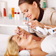 Stock Photo: Tweezing eyebrow by beautician.