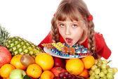 Child with fruit and vitamin pill. — Stock Photo