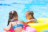 Children sitting on inflatable ring in water. — Stock Photo
