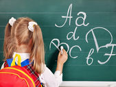 Schoolchild writting on blackboard — Stock Photo