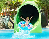 Kind op wasser rutsche op aquapark. — Stockfoto