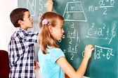 School child writting on blackboard. — Stockfoto