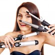 Foto Stock: Womholding iron curling hair.