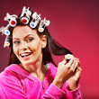 Stock Photo: Woman wear hair curlers on head.