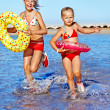 Children holding hands running on beach. — Stock Photo #27608335