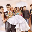 Stock Photo: Groom carries bride on his hands .