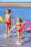Niños corriendo en la playa de la mano. — Foto de Stock