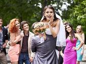 Groom carries his bride over shoulder. — Stock Photo