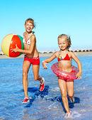 Children holding hands running on beach. — Stock Photo