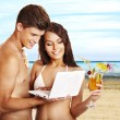 Couple with laptop at beach. — Stock Photo
