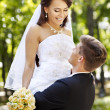Bride and groom with flower outdoor. — Stock Photo