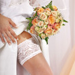 Garter at leg of bride. — Stock Photo