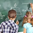 School child writting on blackboard. — Stock Photo #29031657