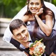 Groom carries his bride over back. — Stock Photo
