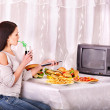 Stock Photo: Womeating fast food and watching TV.