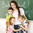 Stock Photo: Children in classroom near blackboard.