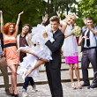 Groom carries his bride over shoulder. — Stock Photo