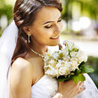 Bride with flower outdoor. — Stock Photo