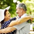 Stock Photo: Happy old couple with flower.