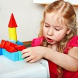 Stock Photo: Child preschooler play wood block in play room.