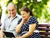 Old couple with tablet pc sit on bench . — Stock Photo