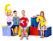 Children sitting at cube. — Stock Photo