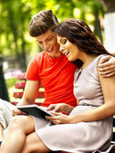 Couple with tablet pc sit on bench . — Stock Photo