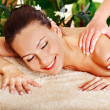 Blond woman getting massage in tropical spa. — Stock Photo